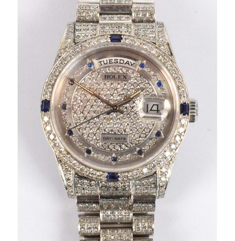 ROLEX; an 18ct white gold day/date wristwatch with diamonds and sapphires set throughout.