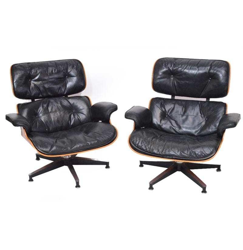 CHARLES AND RAY EAMES FOR HERMAN MILLER; a pair of Charles and Ray Eames for Herman Miller rosewood veneered and black leather upholstered lounge chairs.