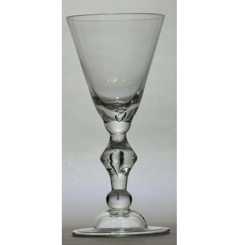 A large early 18th century heavy baluster goblet with wide round funnel bowl above cusp knop set with a tear above domed folded foot, English c.1710.