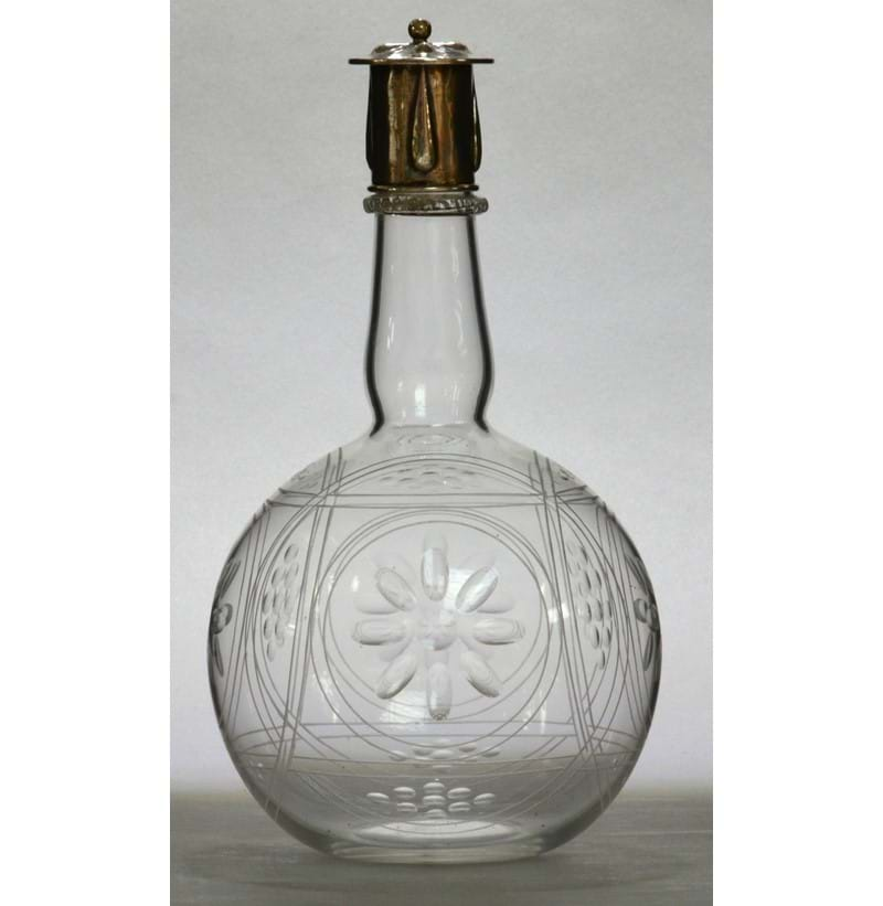 JAMES POWELL WHITEFRIARS; a clear glass bottle form decanter with silver cap designed by Harry Powell.